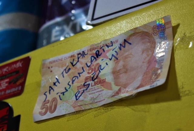 Üzerine 'Sahtekar insanların eseriyim' notunu yazdığı parayı dükkanına astı